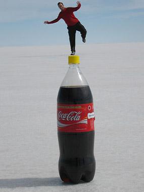 De pie en una gran botella de Cola